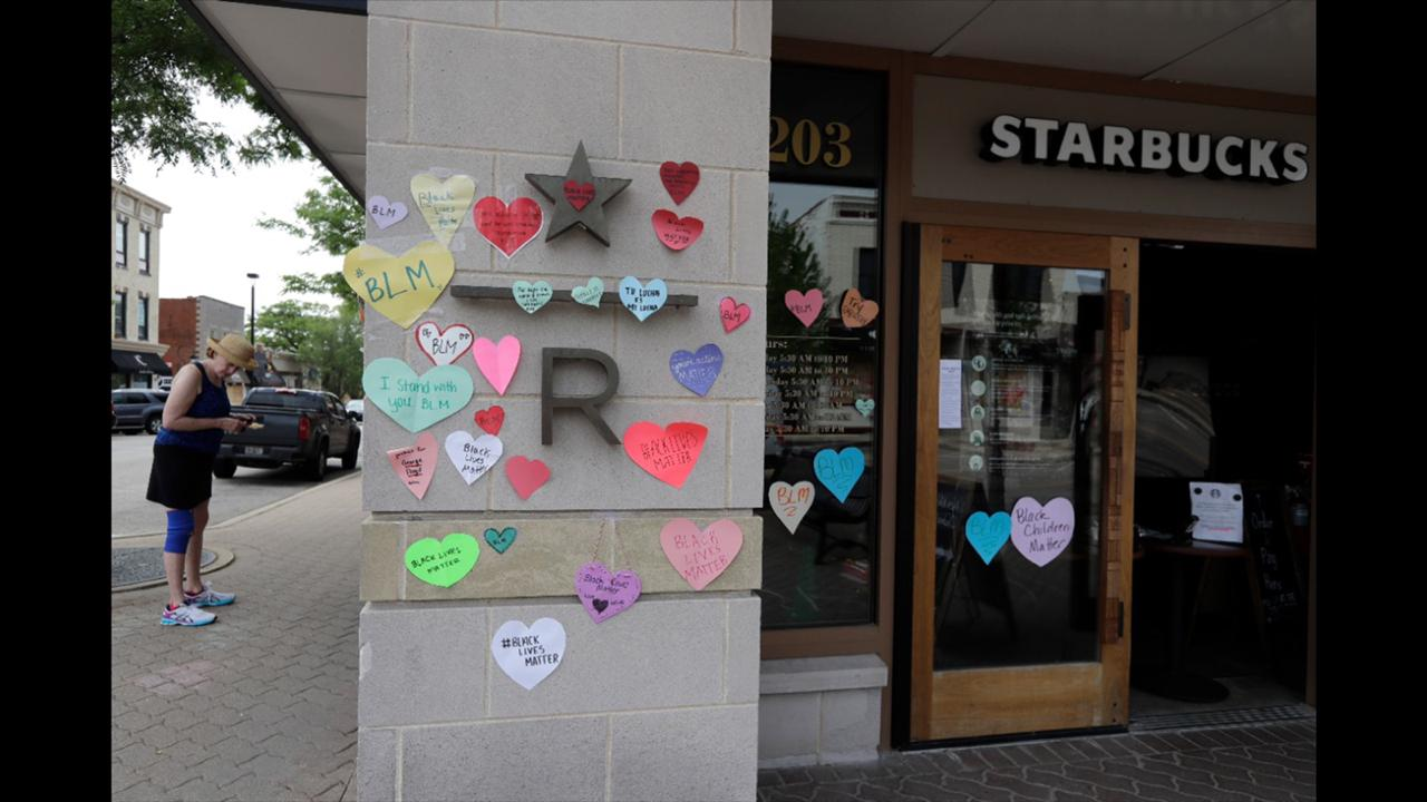 In this Thursday, June 4, 2020 file photo, a woman looks at the plywood covering the windows of a Starbucks store in downtown Naperville, Ill., as Naperville residents used hearts to post messages in support of the Black Lives Matter movement. (AP Photo/Nam Y. Huh, File)