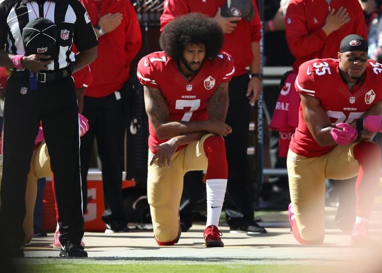 Colin Kaepernick (au centre) s'agenouille avec son partenaire des San Francisco 49ers Eric Reid (droite) pendant l'hymne national avant un match de NFL contre les Tampa Bay Buccaneers le 23 octobre 2016 à Santa Clara, en Californie