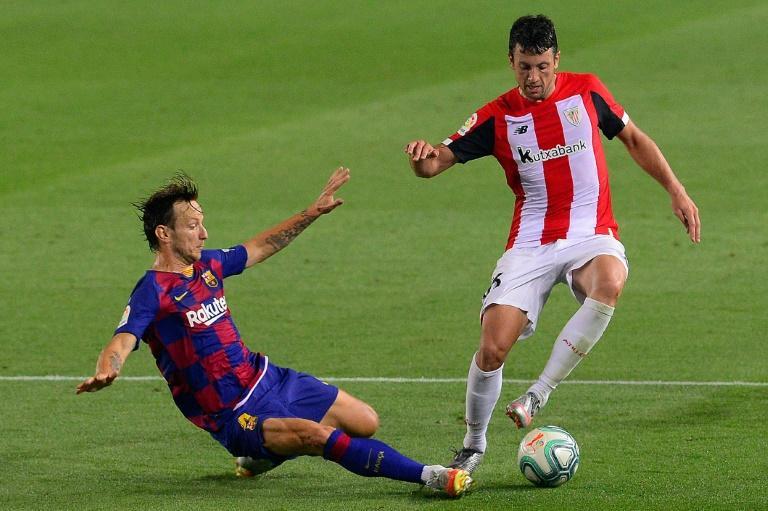 Le milieu de terrain du FC Barcelone Ivan Rakitic (à gauche) tacle Mikel Vesga, de l'Athletic Bilbao, le 23 juin 2020 au Camp Nou