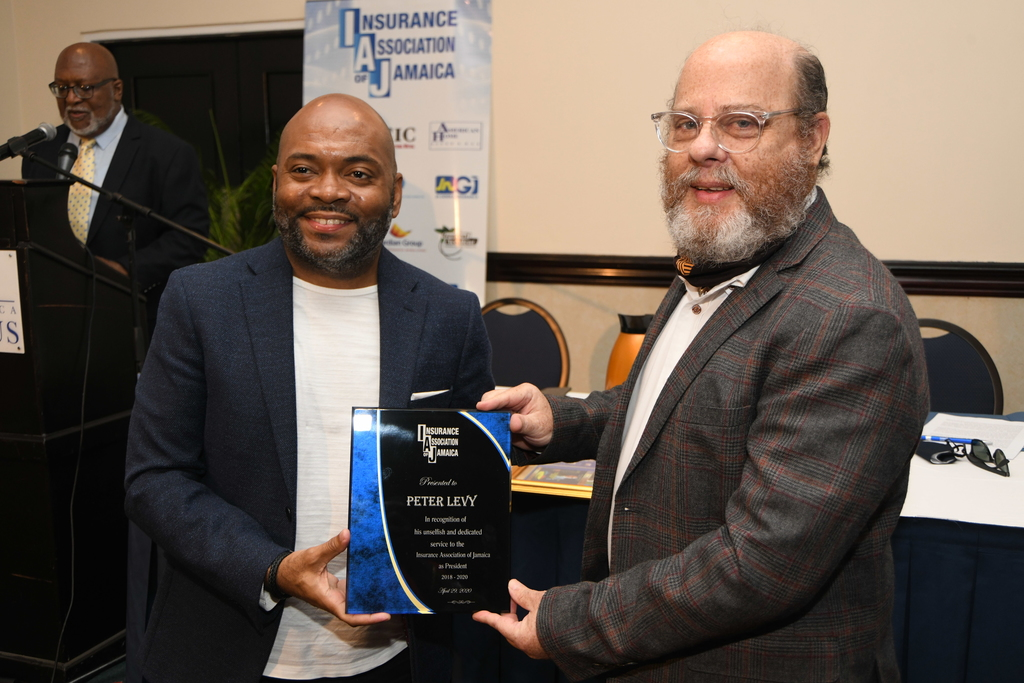 Newly elected president of the Insurance Association of Jamaica, Vernon James (left) presents a plaque to outgoing IAJ president, Peter Levy.
