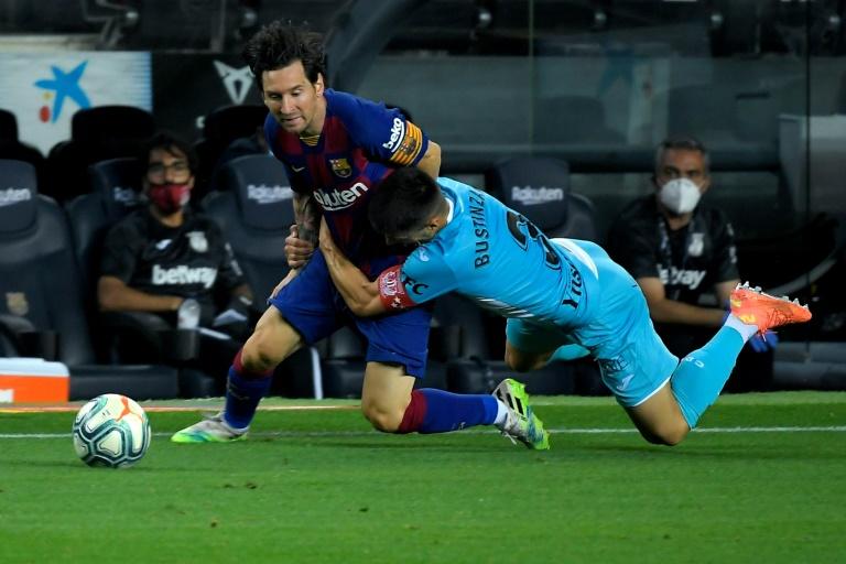 """Lionel Messi, le prodige argentin du Barça, """"plaqué"""" par le défenseur de Leganes Unai Bustinza, lors du match de football opposant les deux équipes au Camp Nou à Barcelone le 16 Juin 2020. LLUIS GENE AFP"""