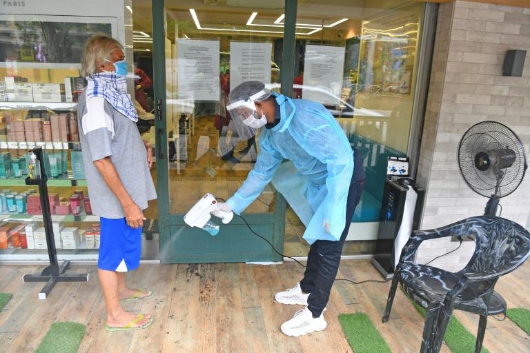 Un employé désinfecte les pieds d'un client avant qu'il entre dans un salon de coiffure, le 28 juin 2020 à Bombay, en Inde