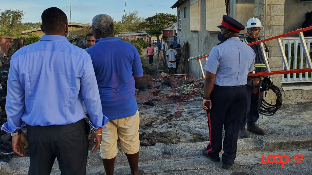 Minister Wilfred Abrahams at the scene with police and fire officers along with Sliver Sands residents and fishermen assisting after the blaze was extinguished.