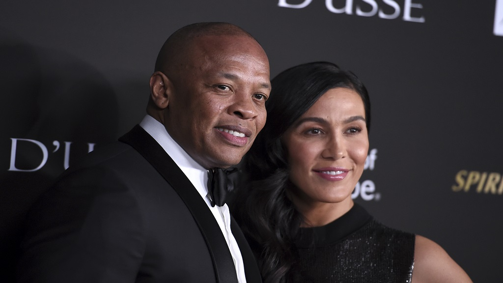 FILE - In a Thursday, October 11, 2018 file photo, Dr. Dre, left, and Nicole Young arrive at the City of Hope Gala, at the Barker Hangar in Santa Monica, California. Dr. Dre's wife of 24 years Nicole Young has filed for divorce. Young filed documents Monday, June 29, 2020 seeking to end her marriage with the producer, rapper and music mogul whose real name is Andre Young in Los Angeles Superior Court.(Photo by Jordan Strauss/Invision/AP, File)