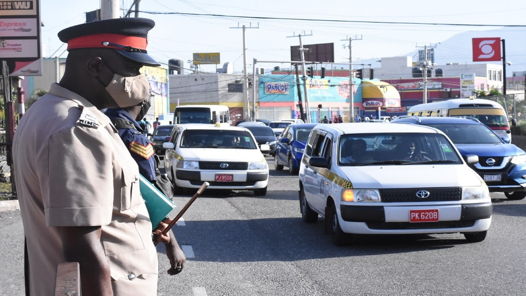 A police inspector observes the traffic flow in Half Way Tree square on Monday. (Photos: Marlon Reid)