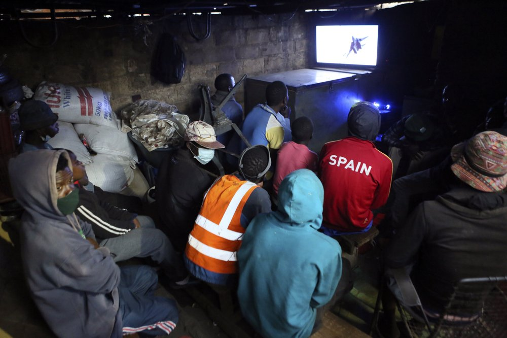 A group of youngsters play a game of cards, in a neighborhood in Harare. Zimbabweans starved for entertainment, including some children, have turned to petty gambling and other activities in poor neighborhoods where many have lost their livelihoods. Some defy social distancing, crowding shoulder to shoulder.  (AP Photo/Tsvangirayi Mukwazhi)