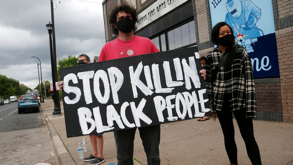 Protesters gather near the site of the death of a man, Tuesday, May 26, 2020, who died in police custody Monday night in Minneapolis after video shared online by a bystander showed a white officer kneeling on his neck during his arrest as he pleaded that he couldn't breathe. (AP Photo/Jim Mone)