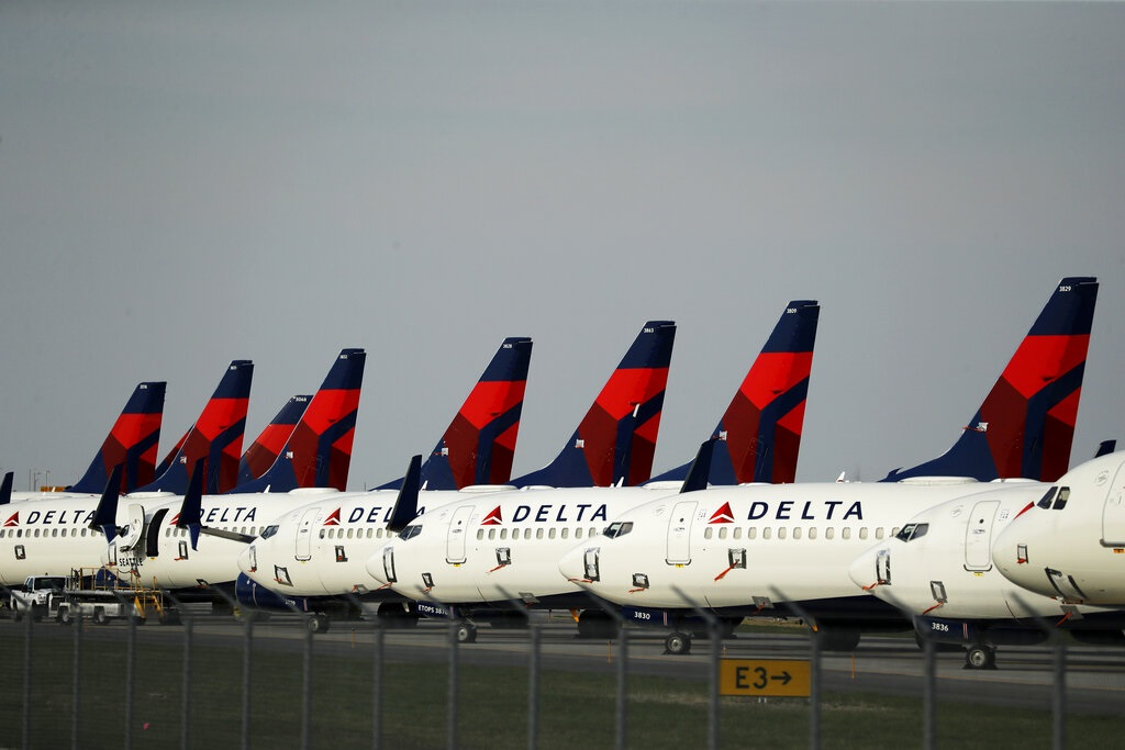 This April 1, 2020 file photo, several dozen mothballed Delta Air Lines jets are parked at Kansas City International Airport in Kansas City. (AP Photo/Charlie Riedel, File)