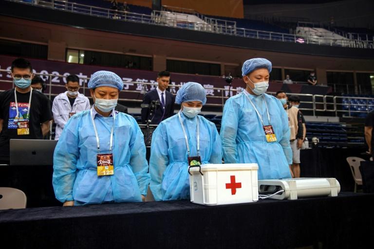 Du personnel soignant rend hommages aux morts du coronavirus avant un match de basketball à Qingdao, le 20 juin 2020