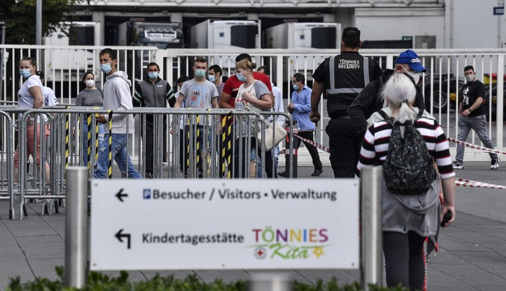 Workers with face masks enter the Toennies meatpacking plant, Europe's biggest slaughterhouse, where the German Bundeswehr army helps to build up a test center for coronavirus in Rheda-Wiedenbrueck, Germany, Friday, June 19, 2020. (AP Photo/Martin Meissner)