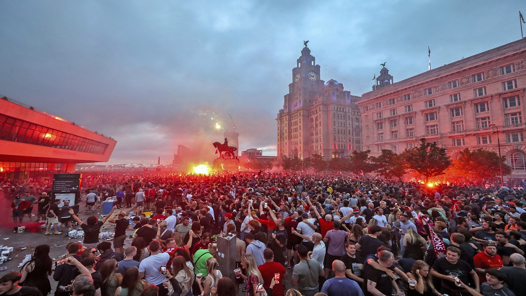 Liverpool fans let off flares outside the Liver Building in Liverpool, Friday June 26, 2020, as they gather and celebrate the team's English Premier League title.  Liverpool were confirmed as champions for the first time since 1990 on Wednesday following Manchester City's 2-1 loss at Chelsea. (Peter Byrne/PA via AP)