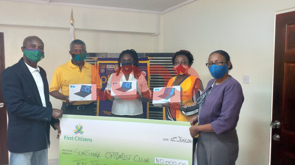 Principal of St George Secondary, Dennis Browne(L) receiving a cheque along with 2 members of the board from Karen Mcclean Bishop from Sunshine Optimist Club (2nd R)and Head of retail and commercial banking at First Citizen's, Cheryl-Ann LaRoche (R)