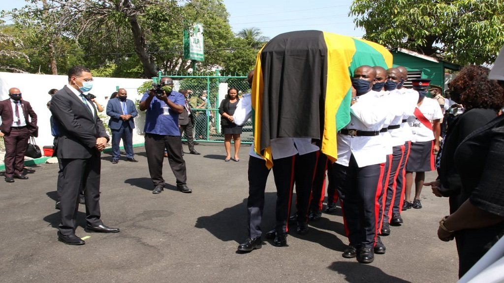 Prime Minister Andrew Holness looks on as members of the JCF carry late Cabinet minister Shahine Robinson's casket at the Jamaica Labour Party Belmont Road headquarters Tuesday morning.