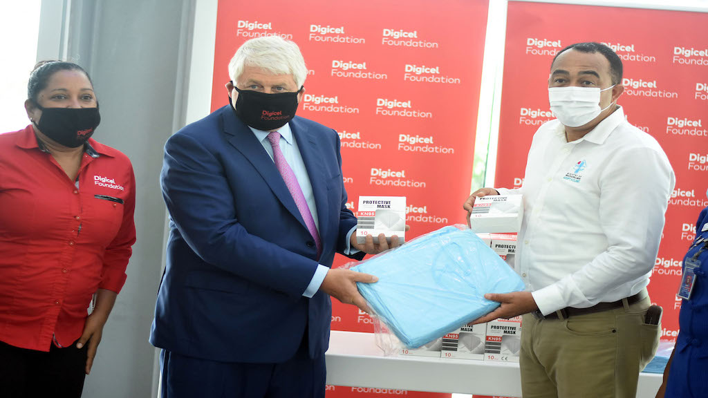Founder and Patron of Digicel Foundation, Denis O'Brien (centre), making the symbolic presentation of personal protective equipment to Health Minister Dr Christopher Tufton on Wednesday at the Digicel headquarters in Kingston. Looking on is Digicel Foundation CEO Charmaine Daniels. (Photos: Marlon Reid)