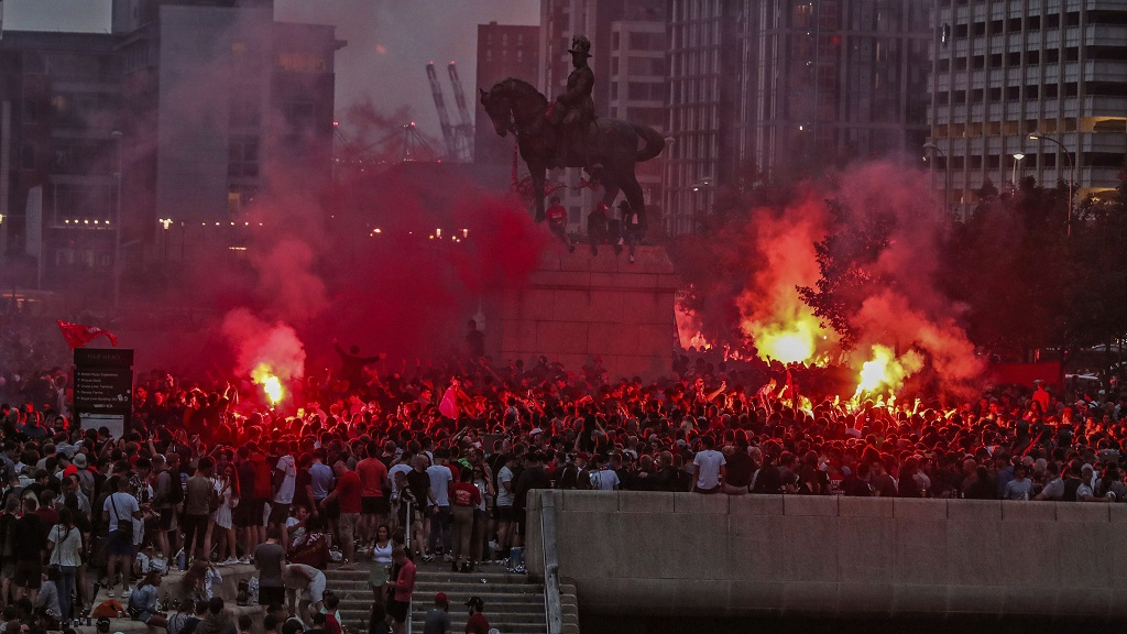 Liverpool football fans let off flares outside the Liver Building in Liverpool, England, Friday, June 26, 2020. Their team clinched the English Premier League title. Liverpool took the title after Manchester City failed to beat Chelsea on Wednesday evening. (Peter Byrne/PA via AP).