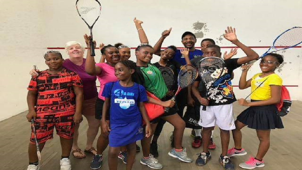 In this photo taken prior to the coronavirus pandemic, young squash players are seen having fun on court with Junior National Programme Manager, Gill Binnie (second left) and coach Fritzroy Smith (fourth right).