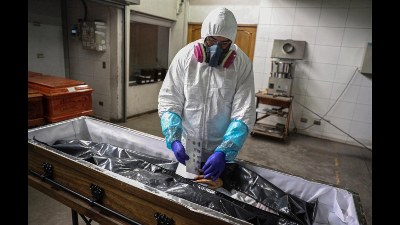 An employee takes the fingerprints of a woman who died from the new coronavirus before her remains are cremated at La Recoleta crematorium in Santiago, Chile, Saturday, June 27, 2020. The Ministry of Health reported on Saturday the highest number of deaths in Chile since the start of the pandemic. (AP Photo/Esteban Felix)