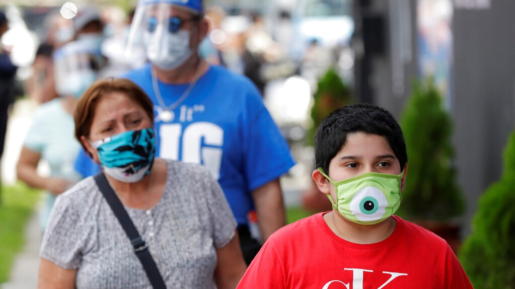 People, social distancing and wearing masks to prevent the spread of the new coronavirus, wait in line at a mask distribution event, Friday, June 26, 2020, in a COVID-19 hotspot of the Little Havana neighborhood of Miami. Florida banned alcohol consumption at its bars Friday as its daily confirmed coronavirus cases neared 9,000, a new record that is almost double the previous mark set just two days ago. (AP Photo/Wilfredo Lee)