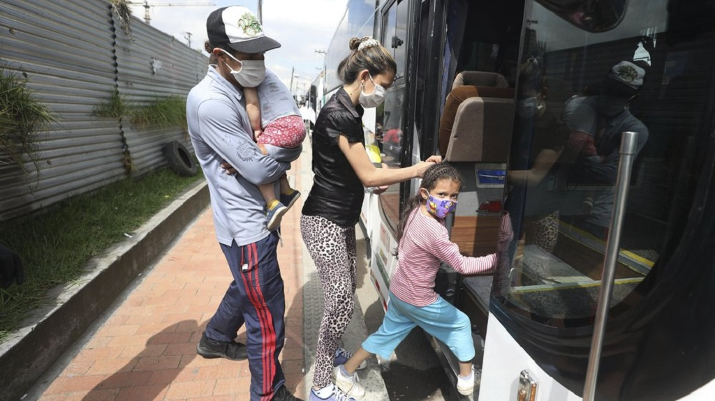 In this April 30, 2020 photo, Venezuelan migrants board a bus departing to the Venezuelan border amid the new coronavirus pandemic, in Bogota, Colombia. The Colombian government say it has paid for some of the bus trips to take the returning migrants to the Venezuelan border. (AP Photo/Fernando Vergara)
