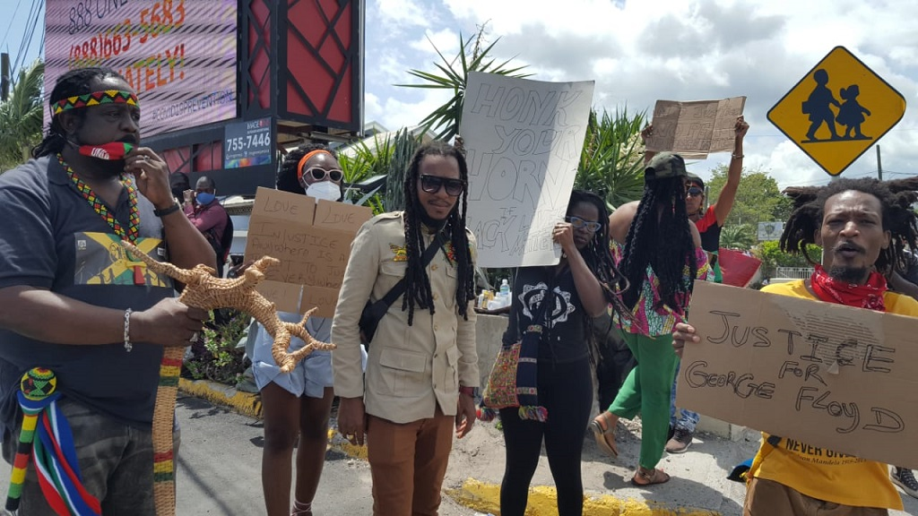 Reggae singer Nature Ellis (centre) leads a group of demonstrators along Constant Spring Road  in protest against the killing of George Floyd, an unarmed black man, by police in the United States.