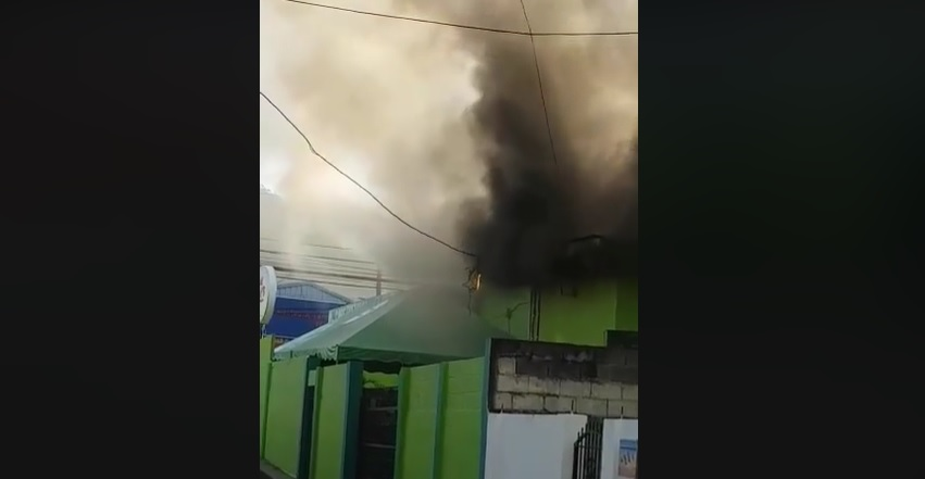 Smoke bellows out of Cap's Bar in Tunapuna during a fire.