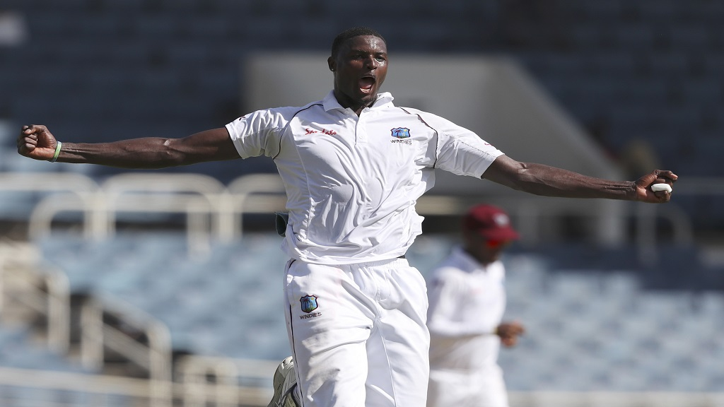 In this Aug. 30, 2019, file photo, West Indies' captain Jason Holder celebrates taking the wicket of India's captain Virat Kohli during day one of the second Test cricket match at Sabina Park cricket ground in Kingston, Jamaica. The West Indies cricket team departed from Antigua on Monday, June 8, 2020 for a three-test tour of England with the entire touring party based in the Caribbean having returned negative tests to COVID-19. (AP Photo/Ricardo Mazalan, File).
