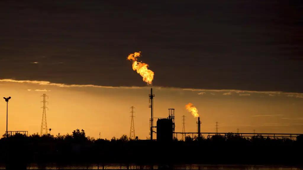 FILE- In this Feb. 18, 2015, file photo, flames burn at an oil complex near El Tigre, Venezuela. (AP Photo/Fernando Llano, File)