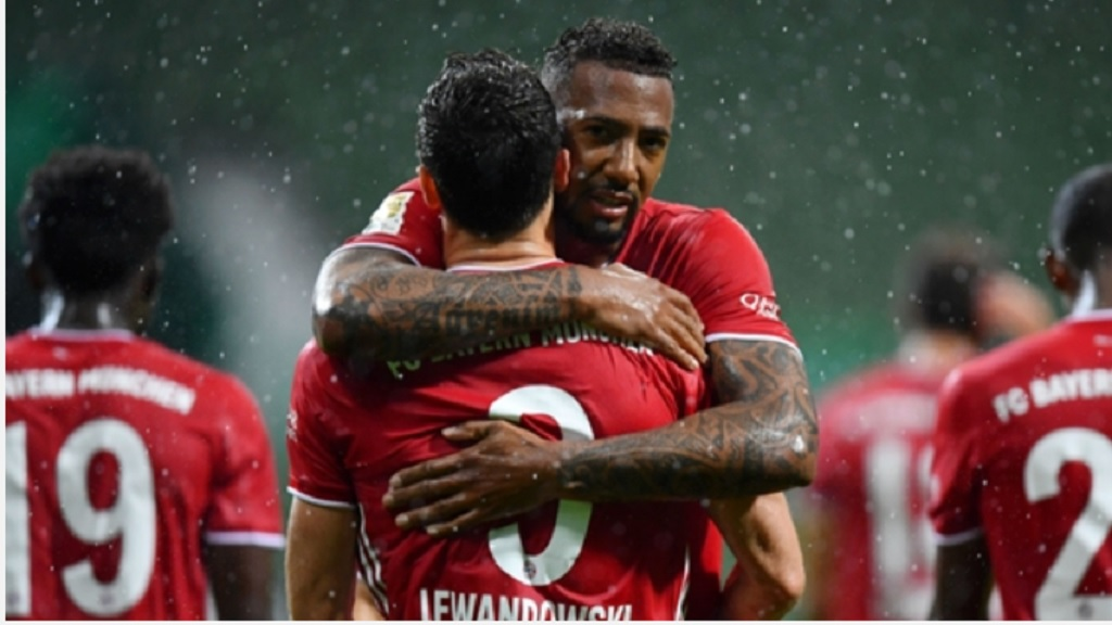 Bayern Munich's Jerome Boateng embraces is teammate Robert Lewandowski who scored the only goal of the German Bundesliga football match against Werder Bremen in Bremen, Germany, Tuesday, June 16, 2020.