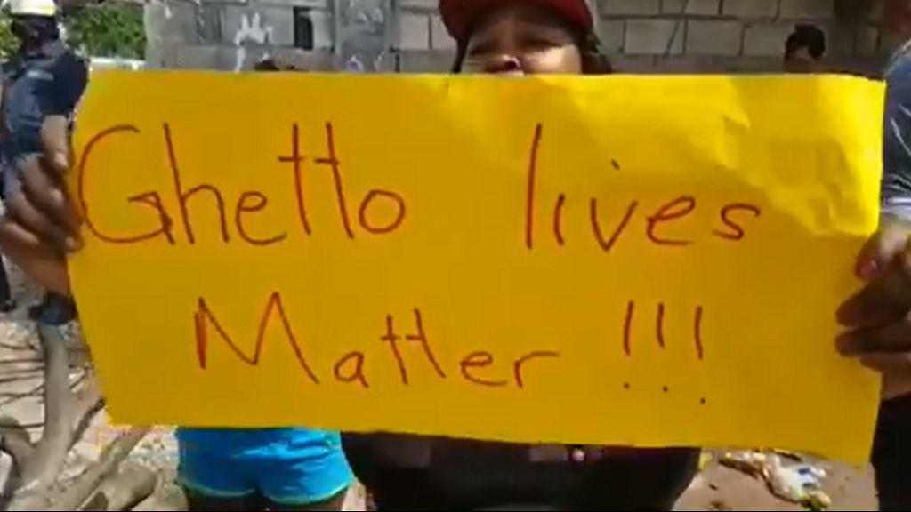 "A Cockburn Gardens resident with a ""Ghetto Lives Matter"" placard following the fatal shooting of a man during a reported police operation on Friday morning."