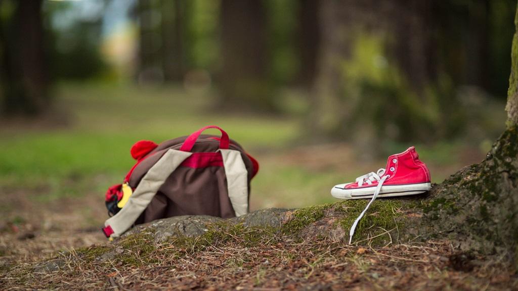 iStock image of a child's backpack and shoe left behind in a wooded park.