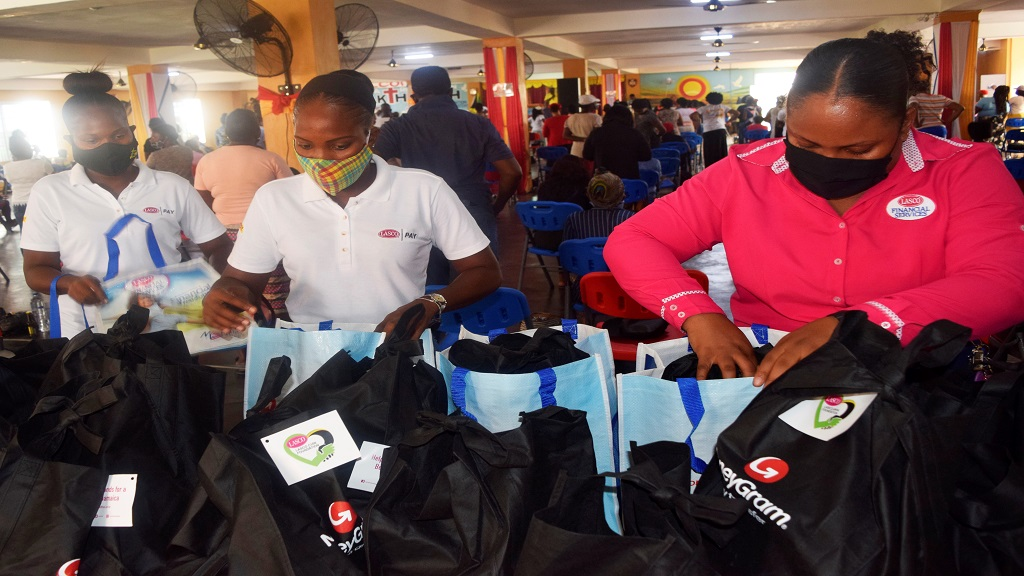 Lasco Financial Services Limited Sponsorship and Promotions Officer Nikeisha Alexander (right) and Lasco Money Brand Ambassadors prepare donation packages filled with personal care and food items.