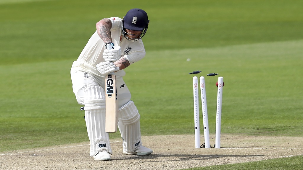 England's Ben Stokes is bowled by West Indies' Kemar Roach during the first day of the third cricket Test match at Old Trafford in Manchester, England, Friday, July 24, 2020. (Martin Rickett/Pool via AP).