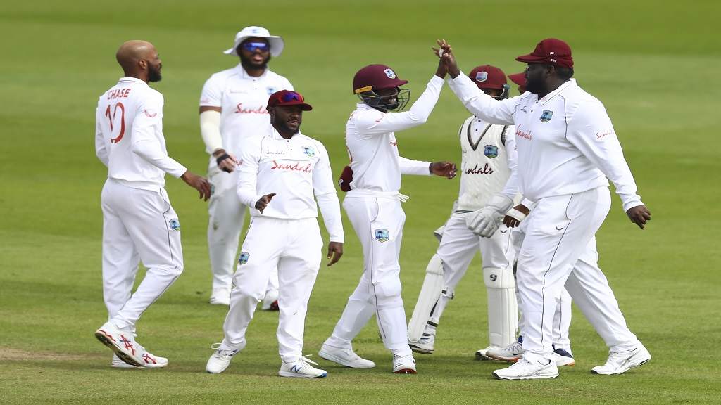 West Indies' Roston Chase, left, and teammates celebrates the dismissal of England's Rory Burns during the first day of the third cricket test match at Old Trafford in Manchester, England, Friday, July 24, 2020. (Michael Steele/Pool via AP).