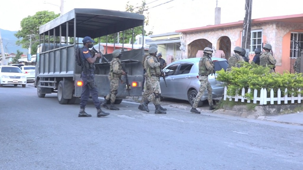 Security personnel entering a premises during a major drug-related operation that involved six communities in Montego Bay, St James on Wednesday.