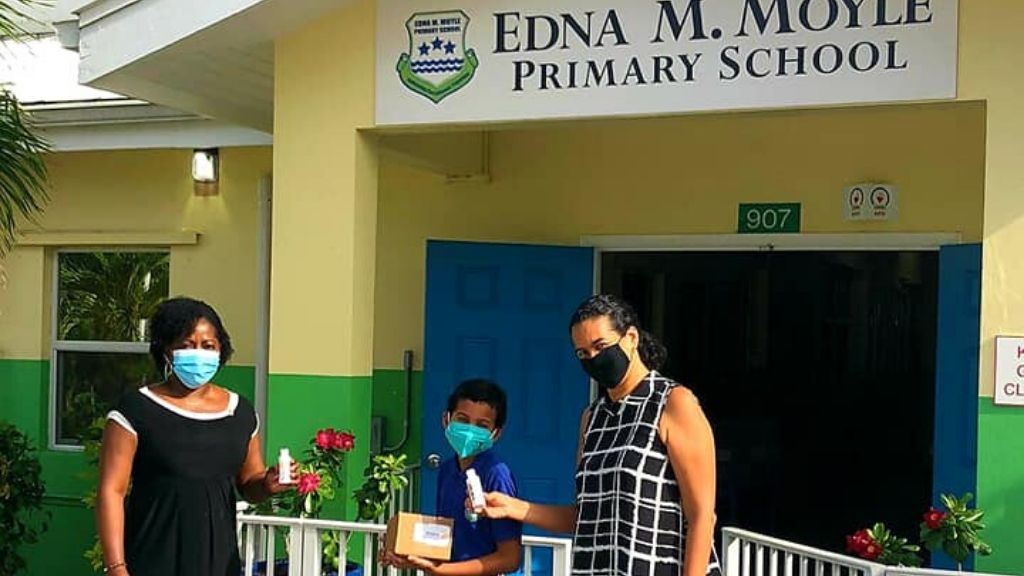 President Stacy Parke presenting hand sanitizers to Edna M. Motley Primary School, in North Side; Image source: Rotary Sunrise