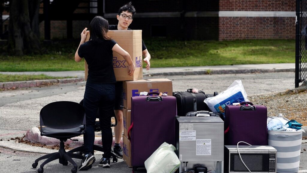 Duke freshman Feng Cong from Singapore and Cassie Lu from Thailand carry a box of their belongings to a pile as they move out of his dorm at Duke University. (Scott Sharpe/The News & Observer via AP)
