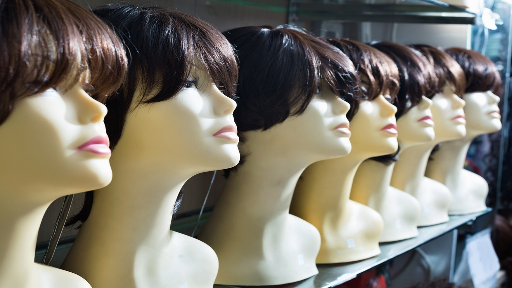 Mannequins with brown-haired and brunet style wigs on shelves. (Photo: iStock)