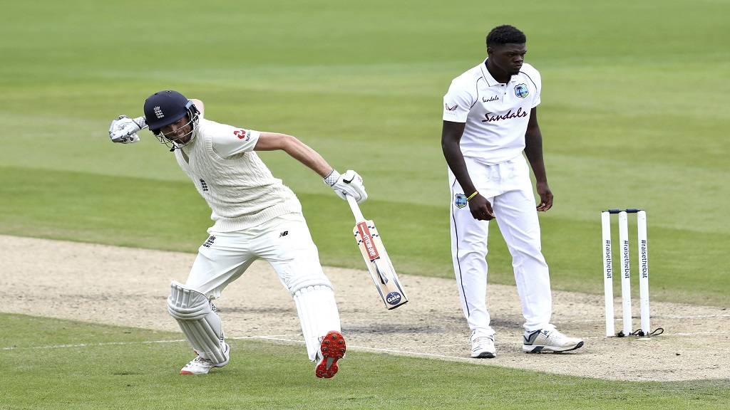 England's Dom Sibley, left, celebrates scoring a century during the second day of the second cricket Test match against West Indies at Old Trafford in Manchester, England, Friday, July 17, 2020. (Michael Steele/Pool via AP).
