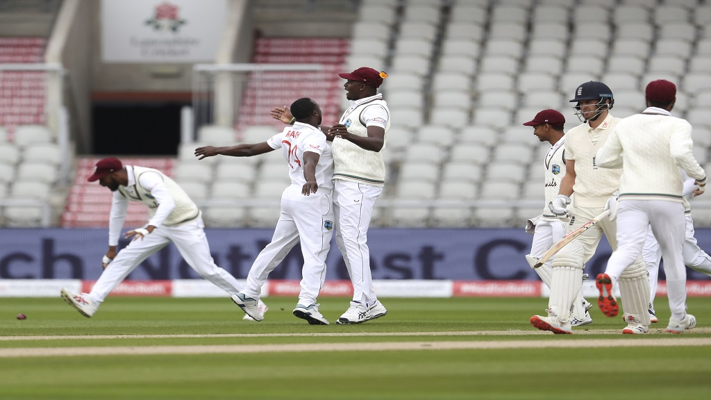 West Indies' Kemar Roach, second left, celebrates with teammates the dismissal of England's Dom Sibley, second right, during the first day of the third and final cricket test match  at Old Trafford in Manchester, England, Friday, July 24, 2020. (Martin Rickett/Pool via AP).