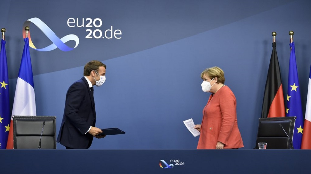 German Chancellor Angela Merkel, right, and French President Emmanuel Macron prepare to address a media conference at the end of an EU summit in Brussels, Tuesday, July 21, 2020. (John Thys, Pool Photo via AP)