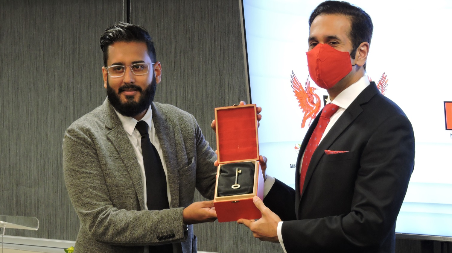 Faris Al-Rawi, Attorney General and Minister of Legal Affairs is presented with the ceremonial key to the Director of Public Prosecution's new office space on Park Street, Port of Spain by Naasir Mohammed, Communications Manager of NIDCO.