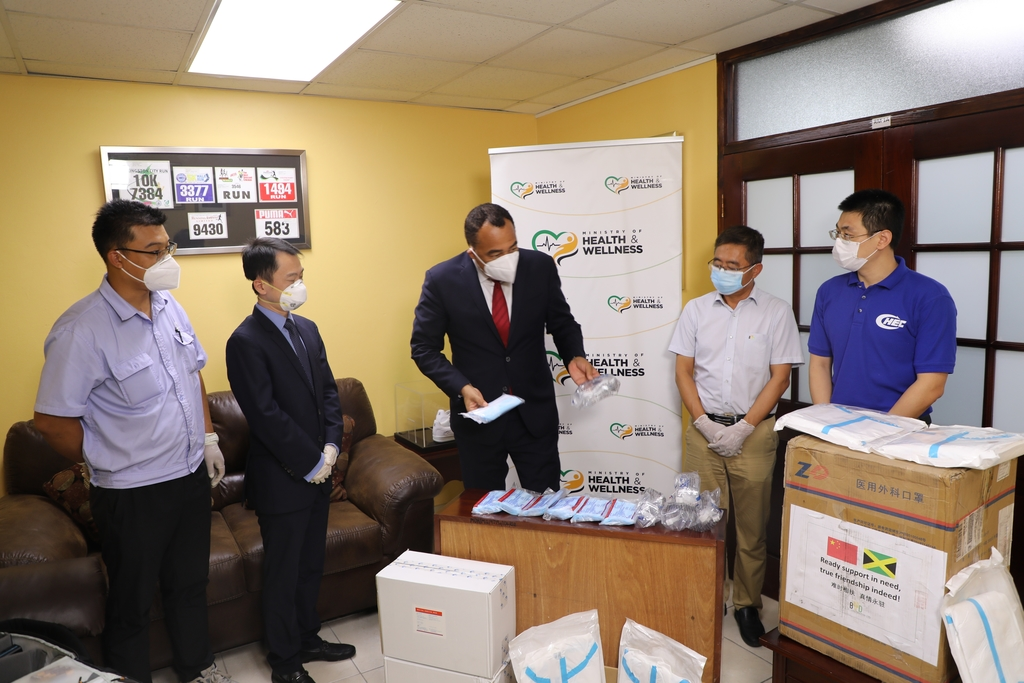 Minister of Health, Dr Christopher Tufton examines surgical masks and other medical equipment donated by the Association of Chinese Enterprises in Jamaica. Looking on are (from left) Jing Sun of JISCO Alpart Jamaica, Andy Deng of Huawei Technologies Jamaica, Richard Xin of BYD Construction and Dangran Bi from China Harbour Engineering Company.