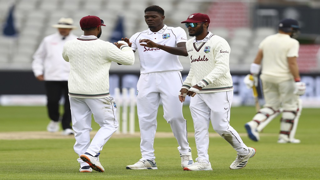 West Indies' Alzarri Joseph, centre, celebrates with teammates the dismissal of England's captain Joe Root during the first day of the second cricket Test match, at Old Trafford in Manchester, England, Thursday, July 16, 2020. (Michael Steele/Pool via AP).