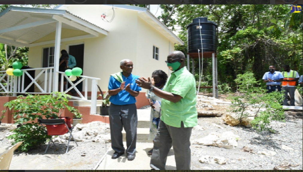 Minister of Local Government and Community Development,  Desmond McKenzie (right), celebrates with beneficiaries of an indigent house (from left): Everald Gibson and his wife, Hazel in Long Road, Portland.
