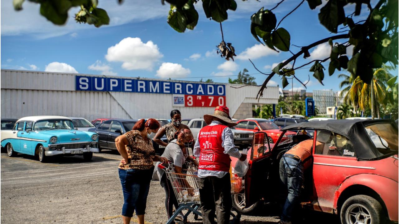Shoppers wearing protective facemasks amid the spread of the new coronavirus load groceries from a dollar store in Havana, Cuba, Monday, July 20, 2020. Cuba has expanded the types of stores that accept dollars for payment to include food stores, as part of the government's effort to capture much needed hard currency to shore up the island's ailing economy. (AP Photo/Ramon Espinosa)