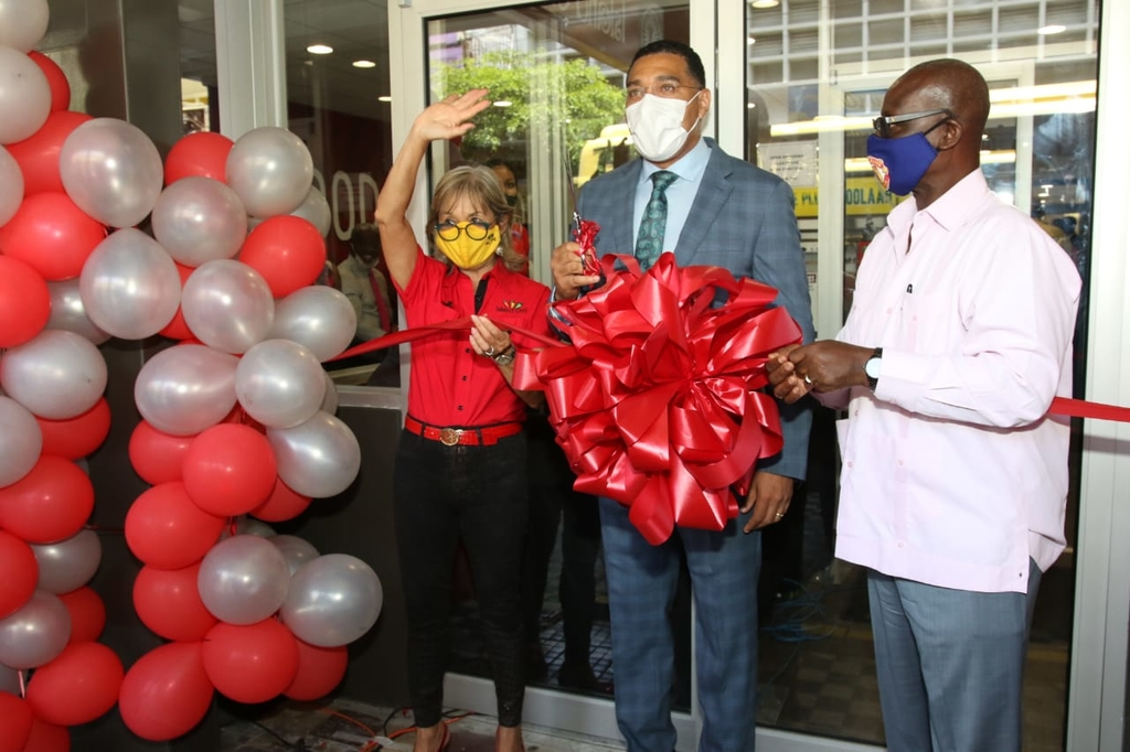 Prime Minister Andrew Holness (centre) and Local Government Minister Desmond McKenzie joined Island Grill CEO Thalia Lyn for the official opening ceremony for the store's new King Street location.