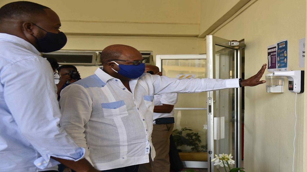 Tourism Minister, Edmund Bartlett (left) adheres to the protocols of a temperature check and hand sanitisation with automated equipment ahead of entering the reception area of Golf View Hotel in Mandeville, Manchester on the weekend. At left is owner/director of Golf View Hotel, Peter Campbell.