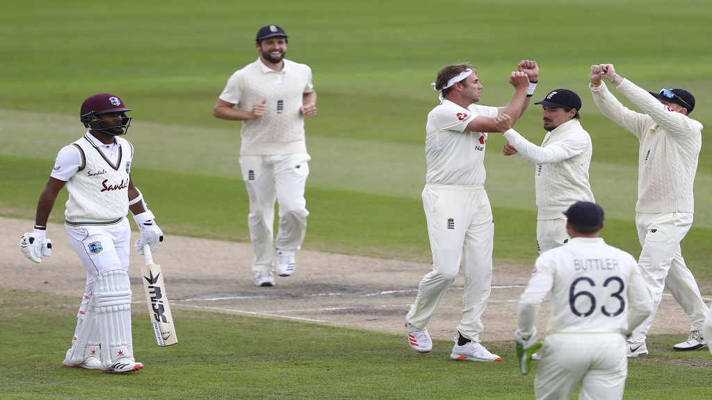 England's Stuart Broad, third right, celebrates the dismissal of West Indies' Kraigg Brathwaite, left, during the second day of the third cricket test match  at Old Trafford in Manchester, England, Saturday, July 25, 2020. (Michael Steele/Pool via AP).