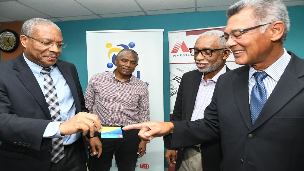 Carlton Barclay (left), CEO, C&WJCCUL shows Peter Chin (right), President of the Alliance Financial Services Limited the new C&WJCCUL/ePay prepaid Mastercard, which is first to market in the credit union movement, while Lennox Robinson (background left), CEO, ePayment Group Limited and Condell Stephenson (background right), President of C&WJCCUL look on.  They were in the Board Room of C&WJCCUL, Half-Way Tree Road on Thursday, July 2.