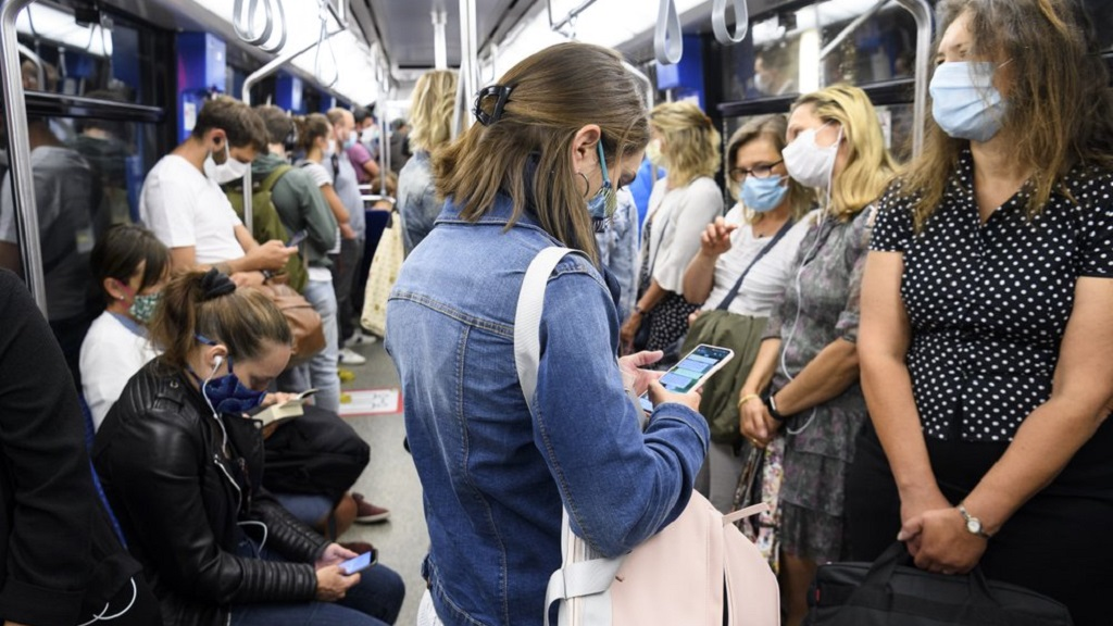 "People wearing protective mask ride the ""Transports publics lausannois"", TL, Metro M2 (underground) during the coronavirus disease (COVID-19) outbreak, in Lausanne, Switzerland, Monday, July 6, 2020. In Switzerland, from Monday 6 July, people aged 12 and over must wear a mask in all public transport, trains, trams and buses, as well as in cable cars and boats. (Laurent Gillieron/Keystone via AP)"